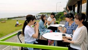 屋外のテラスで夕陽カフェ時間限定コーヒーを楽しむ大学生ら=かほく市二ツ屋で