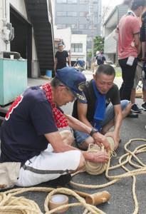 竹を切り出して作った手筒に、縄を巻いて補強する男性=豊橋市札木町で