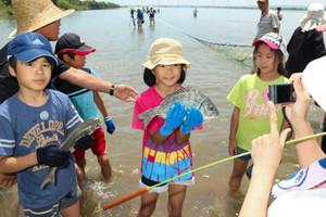 地引き網にかかったクロダイなどの魚をつかむ子どもたち=愛西市の木曽川で