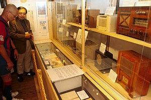 戦時当時の卓上ラジオなど貴重なコレクションが並ぶ会場。右は解説する岡部さん=松本市の日本ラジオ博物館で