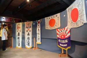 寄せ書きの添えられた日章旗などが並ぶ会場=近江八幡市の旧伴家住宅で