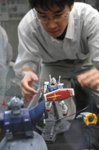 「ガンダム」プラモデルを丁寧に展示する出口恭裕さん=勝山市教育会館で