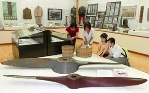戦闘機の木製プロペラなどの展示品を眺める来館者=揖斐川町上南方の揖斐川歴史民俗資料館で