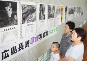 被爆直後の様子を撮影した写真に見入る来館者=揖斐川町乙原の久瀬公正公民館体育館で