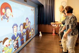 デジタル技術で漫画の世界に入り込むような体験を楽しむ参加者=氷見市中央町で