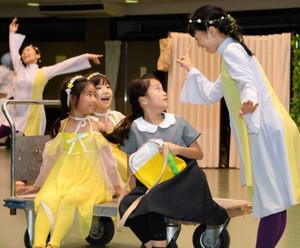 通し稽古で動きを確認する岡田歩佳さん(右から2人目)ら出演者=岐阜市の岐阜メモリアルセンターで