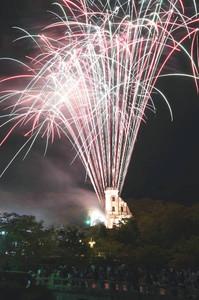 ライトアップされた建造物と夜空を彩る花火=犬山市内山の明治村で