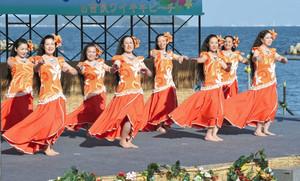 夕日を浴びながら優美なフラを披露する女性たち=西尾市吉良町で