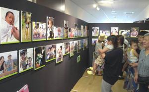 さまざまな写真を見つめる来場者=熊野市井戸町で
