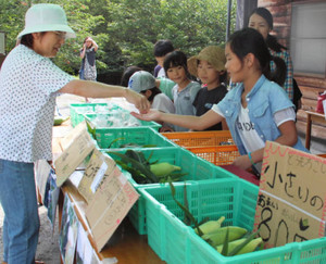 軽トラ市で学校で収穫したトウモロコシを販売する開田小の児童たち=木曽町の「五本松」で