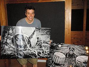 鳥羽志摩地域の海女の写真パネルを手にするブライアン・ミラーさん、右のパネルは韓国の海女=鳥羽市浦村町の海の博物館で