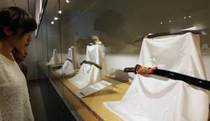 高倉健さん寄贈の日本刀を鑑賞する女性=坂城町の鉄の展示館で