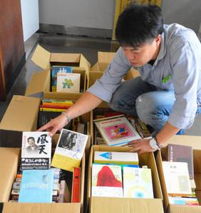 住民から寄せられた販売用の古本を整理する実行委員=伊那市高遠町で
