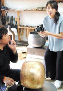 作業をする島谷好徳さん(左)を撮影する舞川あいくさん=高岡市千石町で