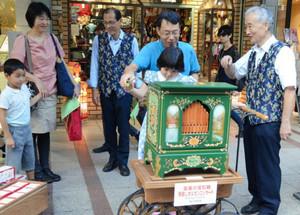 手回しオルガンの魅力を伝える山本耕三さん(右)と後藤洋さん(左から3人目)=静岡市葵区呉服町で