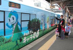 見送りを受けて出発する嶺南6市町のキャラクターが描かれたラッピングトレイン=敦賀市の敦賀駅で