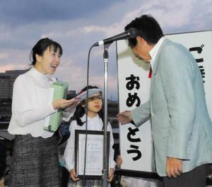 細江茂光市長(右)から記念品を受け取った粥川美乃さん(左)と李朋さん=岐阜市湊町で