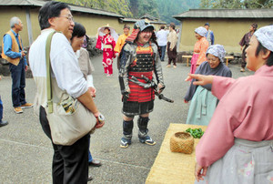 武士にふん装する体験もあり、タイムスリップ気分を堪能する観光客ら=福井市の一乗谷朝倉氏遺跡復原町並で