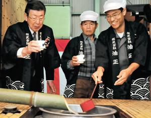 完成した新酒の味を確かめる杜氏の山本隆章さん(中)ら=津市久居本町の油正で
