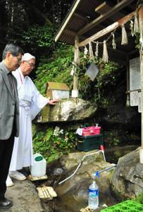 こんこんと湧く「こぶ湯」の魅力を話す宮司の杉一彦さん(右)ら=津市白山町南家城の家城神社で
