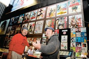 懐かしい映画のポスターやパンフレットの前で、訪れた人と談笑する氷見昭和館の蔵田幹善館長(左)=氷見市柳田で
