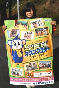 大きなポスターでスタンプラリーをPRする職員=犬山市犬山の日本モンキーパークで