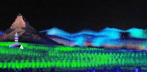 光のカーテンのように水色に輝くオーロラの演出=桑名市の「なばなの里」で