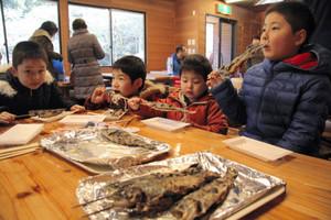 釣ったニジマスをほおばる子どもたち=米原市の県醒井養鱒場で
