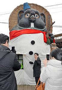雪だるま姿で観光客らを出迎えるタヌキのモニュメント=甲賀市信楽町で