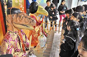 豪華に着飾った「恐竜ひな人形」を興味深そうに見入る園児たち=勝山市の県立恐竜博物館で