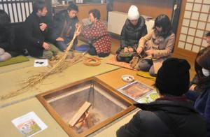 囲炉裏を囲んでガイドボランティアから話を聞く観光客ら=南砺市の菅沼合掌造り集落で