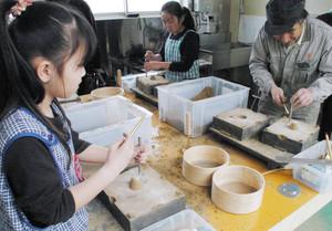 体験工房で鋳物づくりをする児童ら=高岡市戸出栄町で