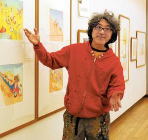 自作の前で、子どもが楽しめる絵本について語る荒井良二さん=砺波市美術館で