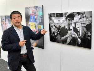 メモを取る吉沢さんを撮影した写真について語る大西さん=岐阜市学園町のぎふ清流文化プラザで