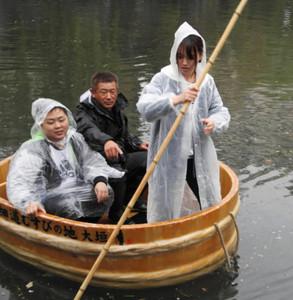 雨の中、本番に向けて船頭の練習をする学生=大垣市の水門川で