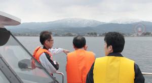 船上から立山連峰や海岸の町並みを望む乗船者たち=富山湾で