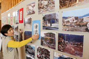 被災直後を記録した写真の説明をする松浦さん=尾鷲市向井の県立熊野古道センターで