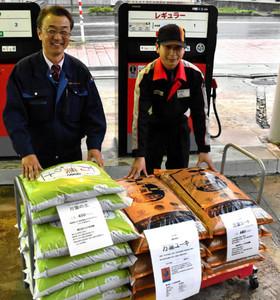 家庭菜園向け肥料をガソリンスタンドで販売する草島周司さん(左)ら=高岡市伏木一宮で