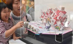 「不思議の国のアリス」の飛び出す絵本で遊ぶ園児ら=県こどもみらい館で