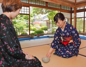 来館者に抹茶を振る舞う鵜瀬さん(右)=日野町の旧山中正吉邸で