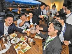 夜景をバックにビールで乾杯する会社員ら=福井市のホテルリバージュアケボノで