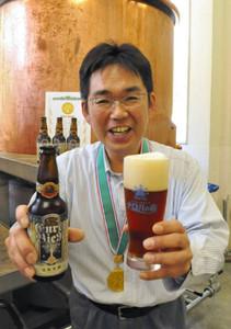 金賞に輝いた地ビール「塩嶺麦酒『メルツェン』」を手にする安川さん=塩尻市北小野の「信州塩尻農業公園チロルの森」の地ビール工房で