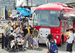 トーマス号(左奥)を背景に7月から運行するバスのバーティーと記念撮影をする親子連れ=島田市金谷東で