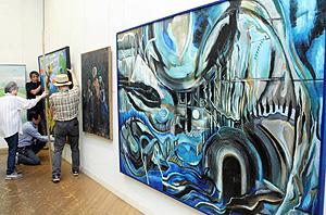 作品の展示作業に励む会員ら=津市の県文化会館で