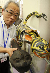 彦根に伝わる張り子の首振りトラ(右)と、トラの首の木型とを比較する藤野さん=彦根市立図書館で