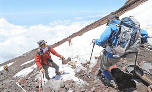 富士山頂下の残雪に覆われた登山道を歩く登山客=27日午前11時9分、静岡県の富士山富士宮口登山道で
