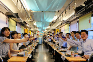 今年初日のビア電で乾杯する乗客たち=近江鉄道提供