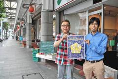 商店街でナイトマーケットのポスターを持つ小松理事長(右)と内田前理事長=沼津市上土町で
