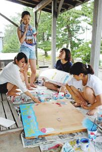 海の家の看板やメニュー表を作る昭和女子大の学生たち=朝日町のヒスイ海岸で