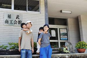 映画祭を開く旧稲武商工会館前で来場を呼び掛ける松島さん夫妻と子どもたち=豊田市稲武町タヒラで